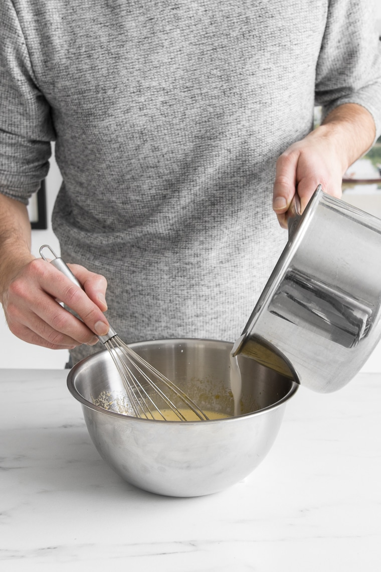 Pouring milk from a saucepan into eggs while whisking