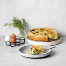 Broccoli and Goat Cheese Quiche with Slice on a Grey Plate