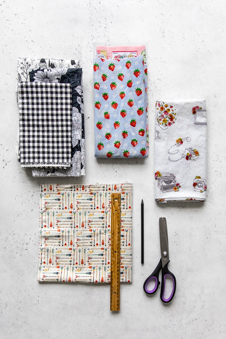 Various pieces of fabric laid out on a table with scissors, pencil and ruler