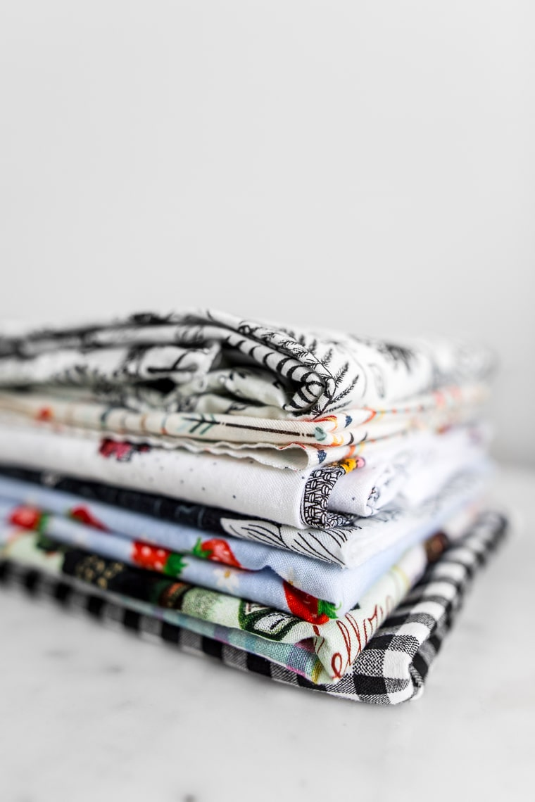 A stack of fabric with various patterns and colours close up