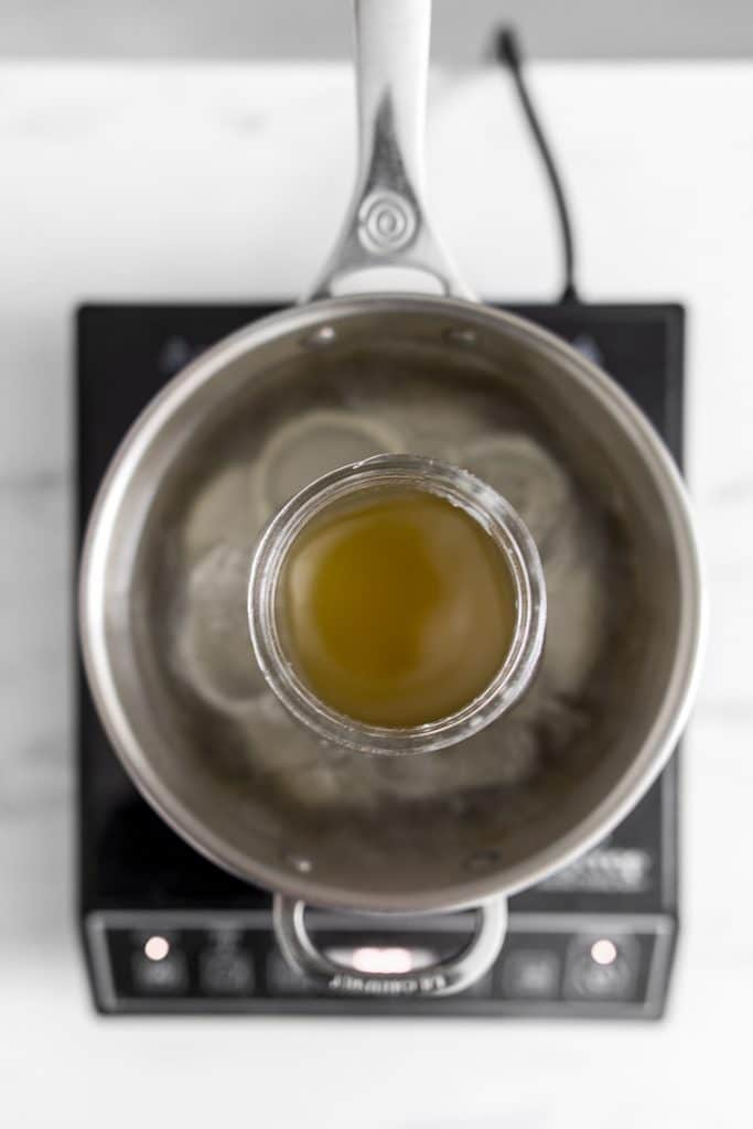 Photo from above of a jar in a pot of water with melted beeswax inside