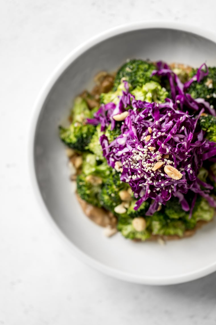 Overhead photo of broccoli salad with red cabbage on top