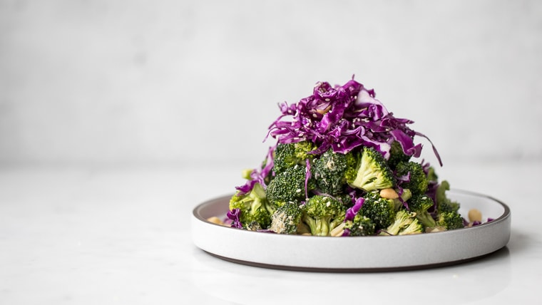 Raw Broccoli Salad with Peanut Butter Dressing and Red Cabbage on a grey plate