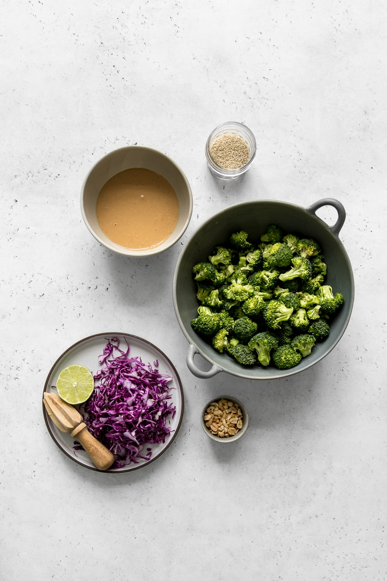 Bowl of Broccoli Florets, Plate with shredded red cabbage and lime half, peanut butter salad dressing, sesame seeds and peanuts