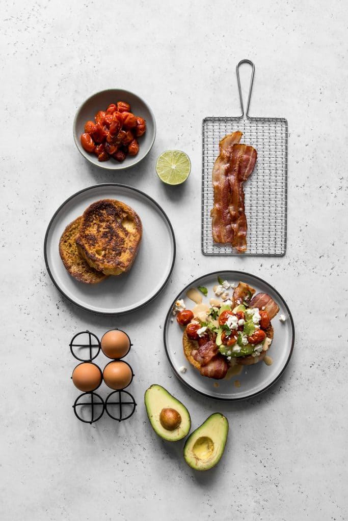 Plates with French Toast, loaded French Toast, eggs, avocados, tomatoes, and bacon