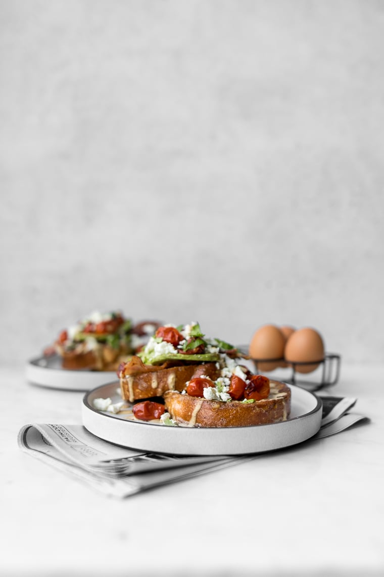 Side view image of savoury french toast topped with avocado, bacon, tomatoes and feta cheese