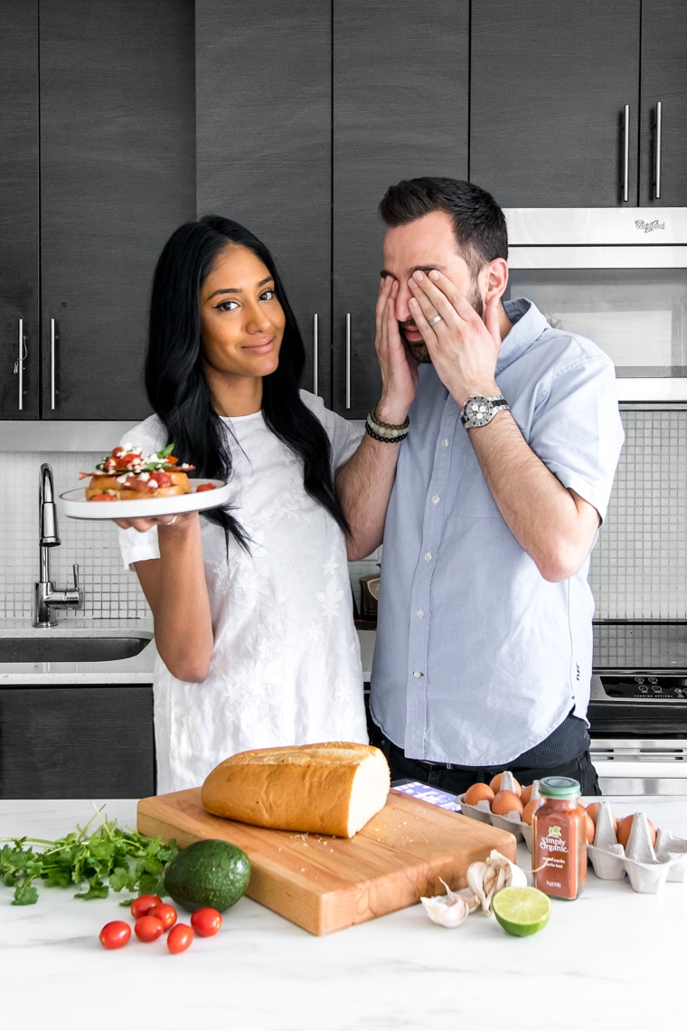 Interracial couple holding plate of French Toast behind a counter with various ingredients