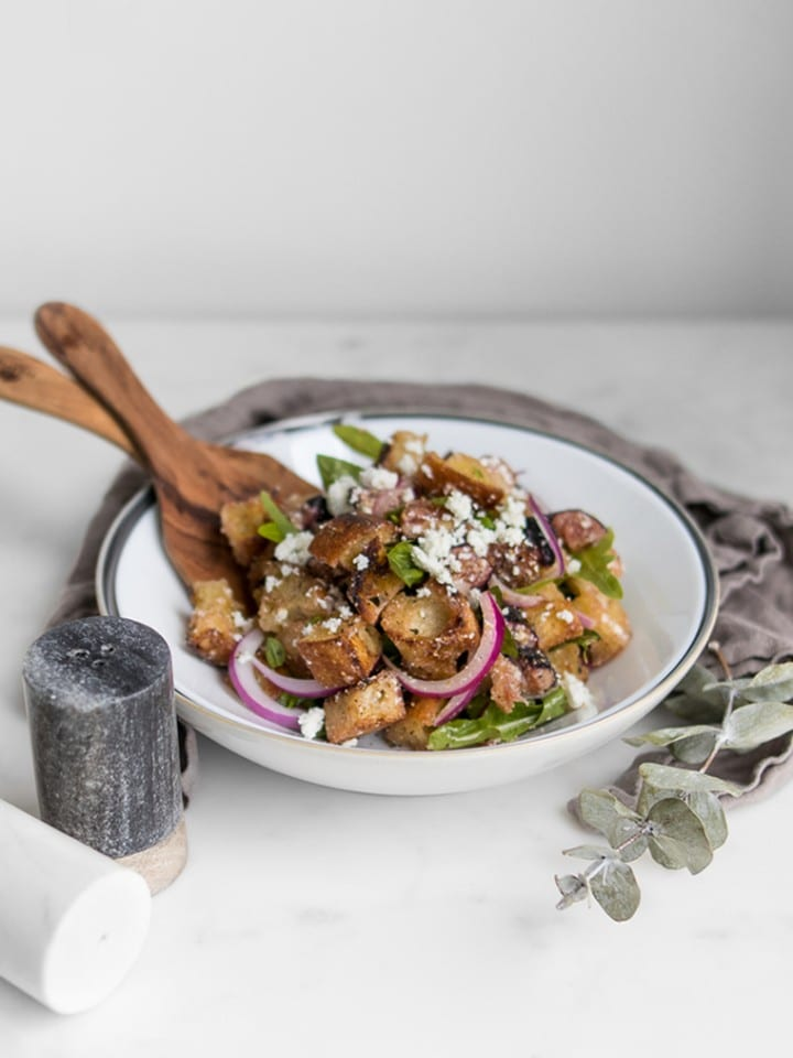 Fig Panzanella Salad in a bowl with tongs next to salt and pepper shakers
