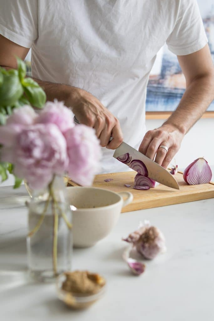 Guy in white shirt slicing red onions on wooden cutting board with pink flowers and bowl in the image