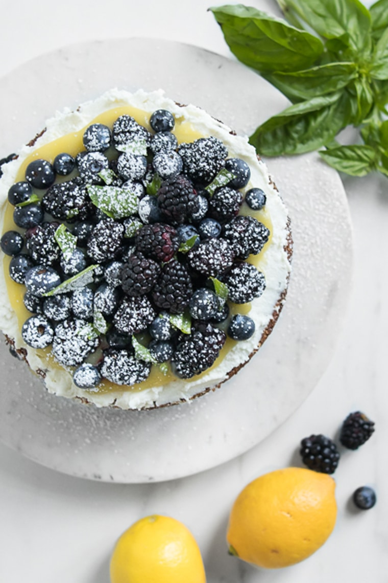 Cake with fresh berries on top next to lemons, blackberries, and basil