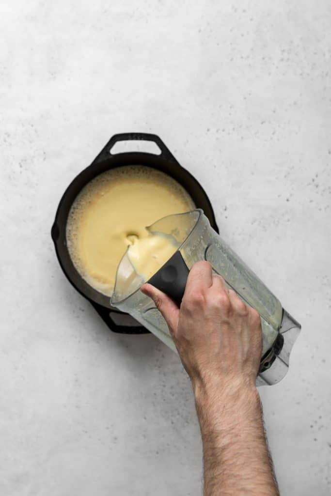Pouring batter from blender into a cast iron skillet