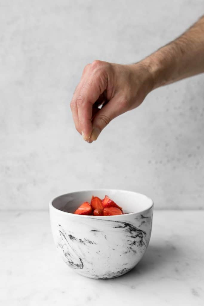 Hand above a marble bowl with strawberries