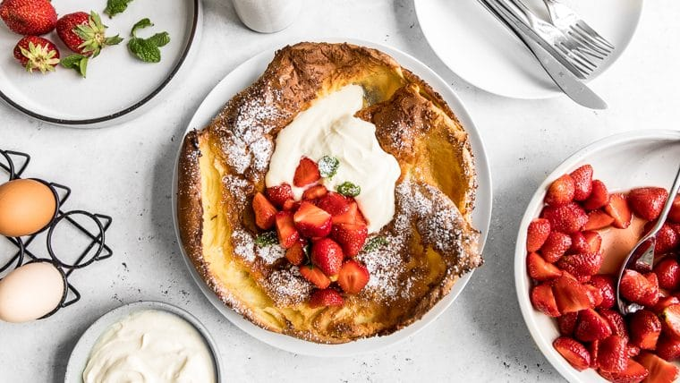 Dutch Baby Pancake with Strawberries and Cream on a Table with bowl of strawberries, eggs, whipped sour cream