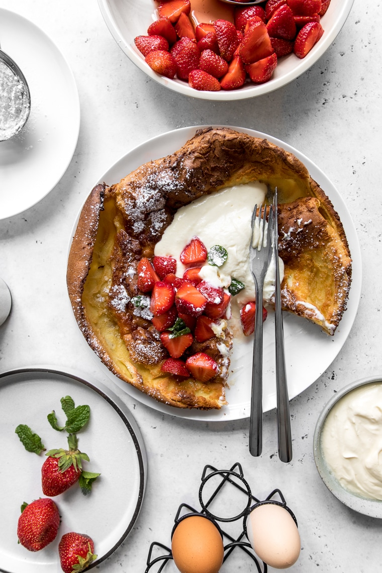 Dutch Baby with Whipped Sour Cream and Strawberries with slice taken and surrounded by strawberries and eggs