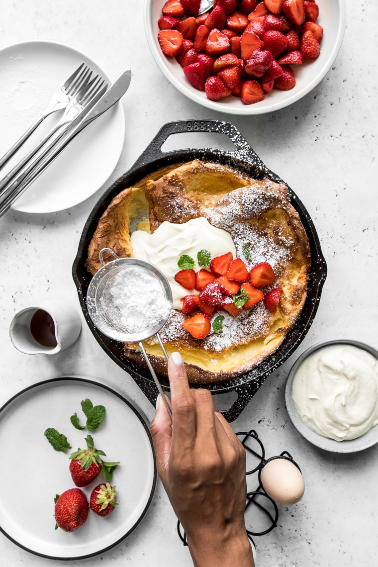 Dutch Baby Pancake with Whipped Sour Cream and Strawberries in a cast iron skillet with hand shaking icing sugar on top