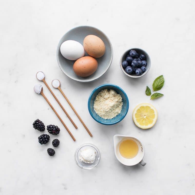 Eggs, berries, almond flour, lemon slices, basil, and honey arranged on a table