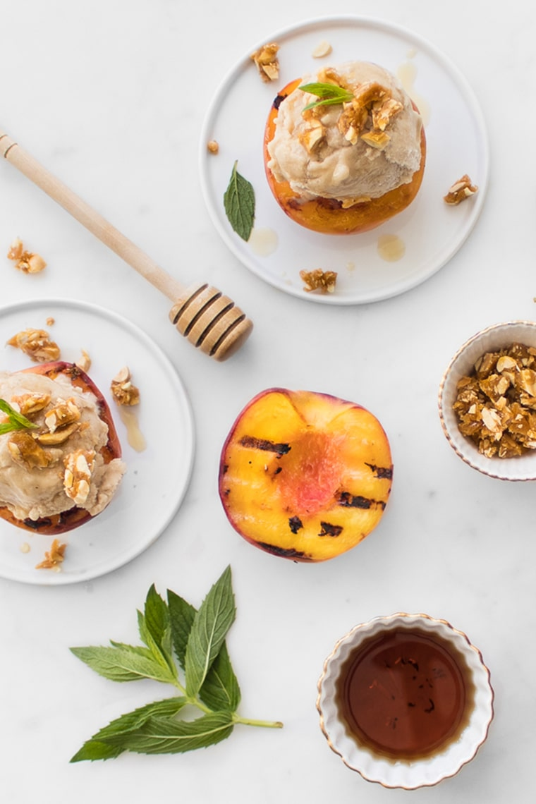 Flat Lay Image of Banana No-Churn Ice Cream on Grilled Peaches, Honey Stick and Bowl of Candied Nuts