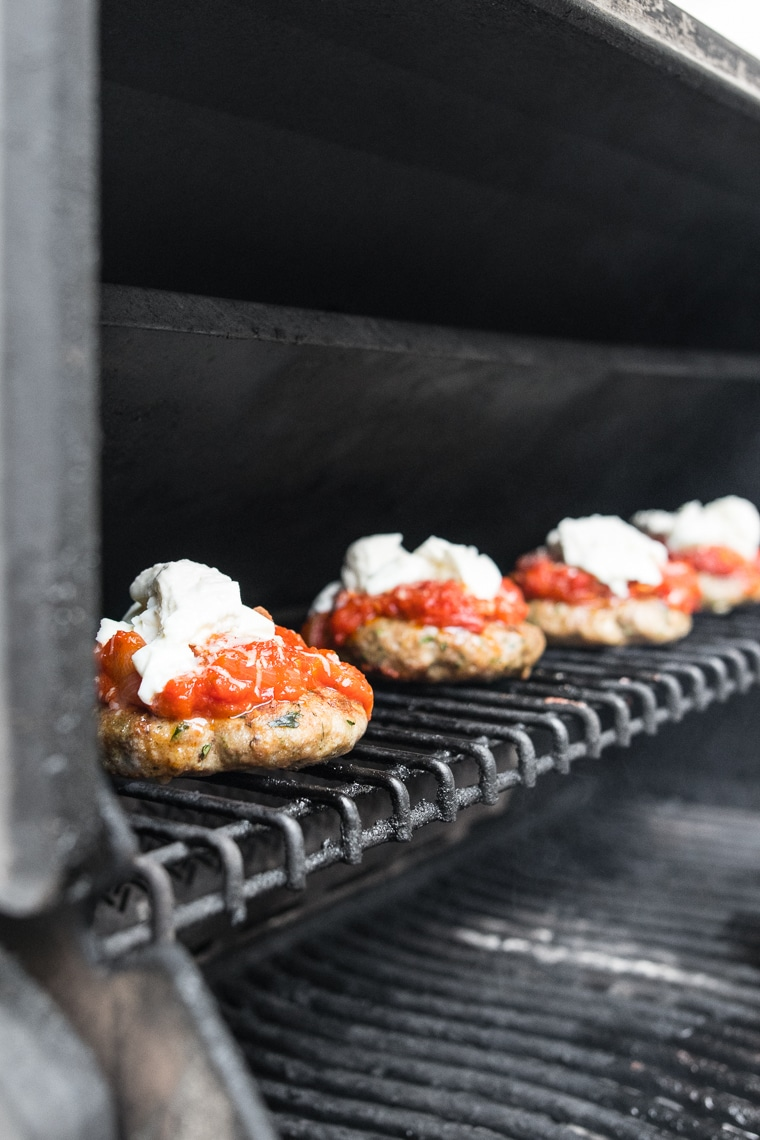 Pork burgers topped with tomato sauce and cheese on the barbecue