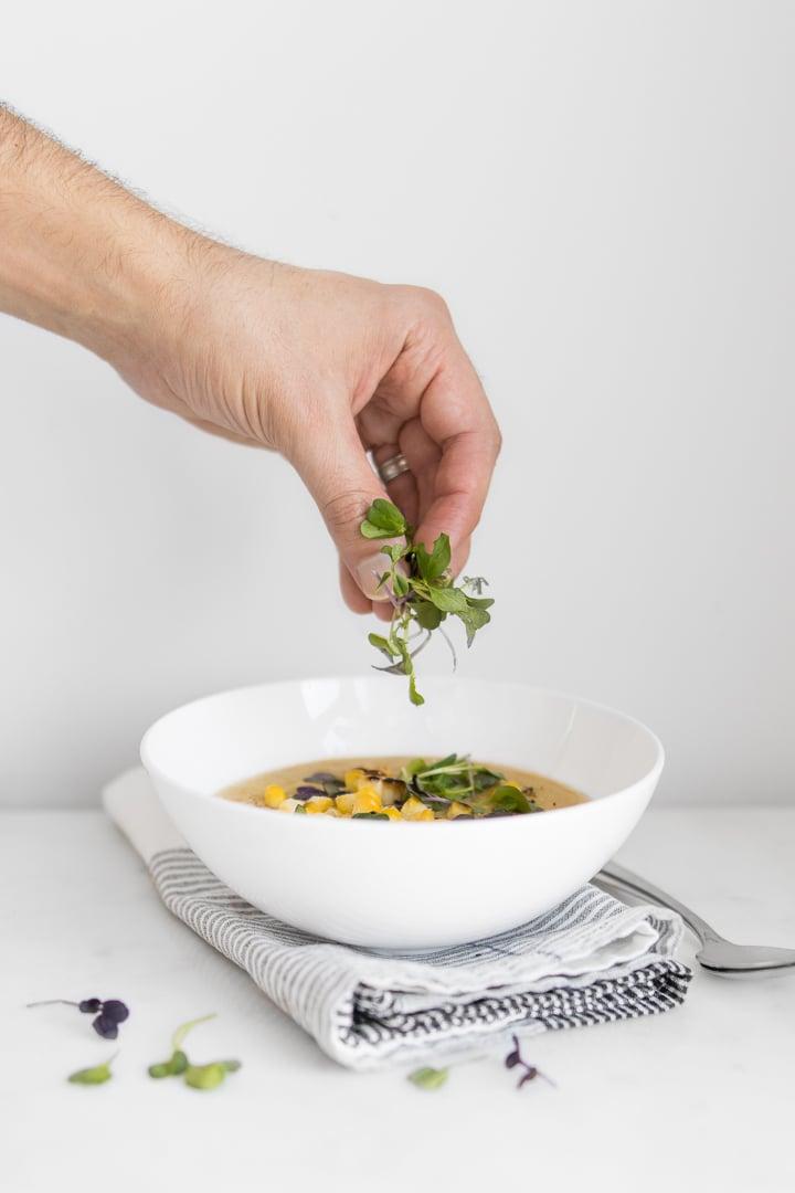 Hand garnishing a bowl of corn soup