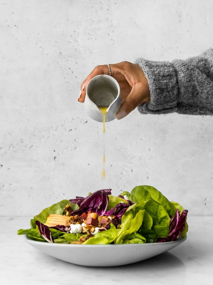 Hand holding container pouring dressing over a butter lettuce and radicchio salad