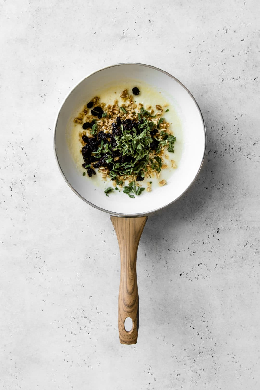 Walnuts, raisins, sage and olive oil in a white frying pan