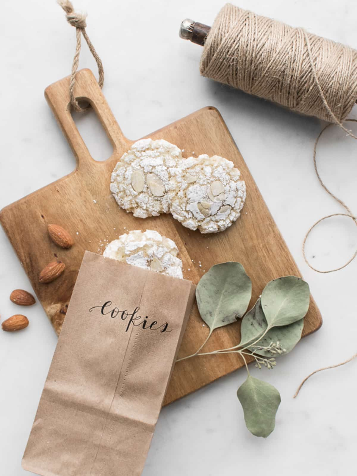 Amaretti Cookies on a wooden cutting board with craft paper bag, leaves, and twine
