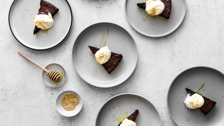 Multiple plates with tahini and chocolate flourless cake with whipped cream and sesame seeds