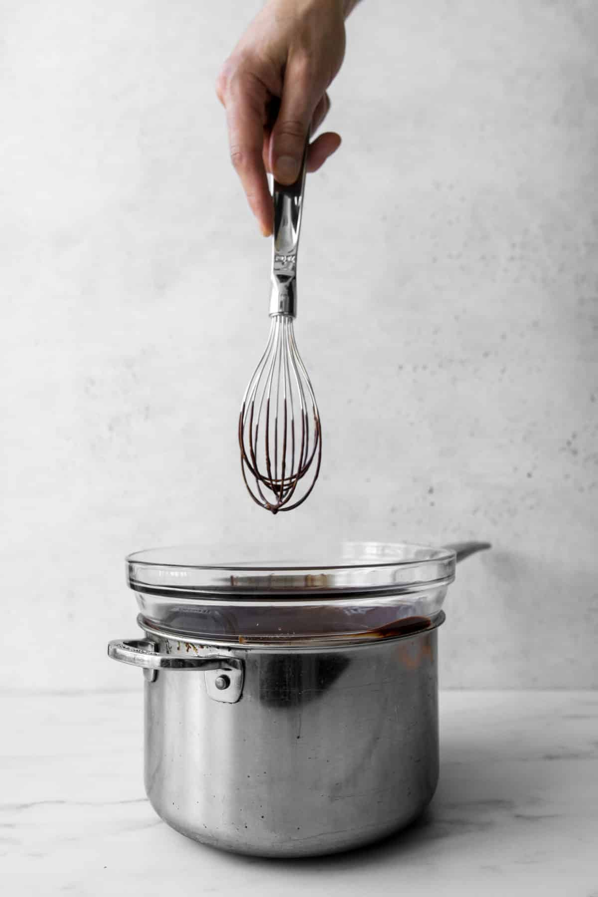 Whisk with chocolate on it being held above a pot with a glass bowl on top