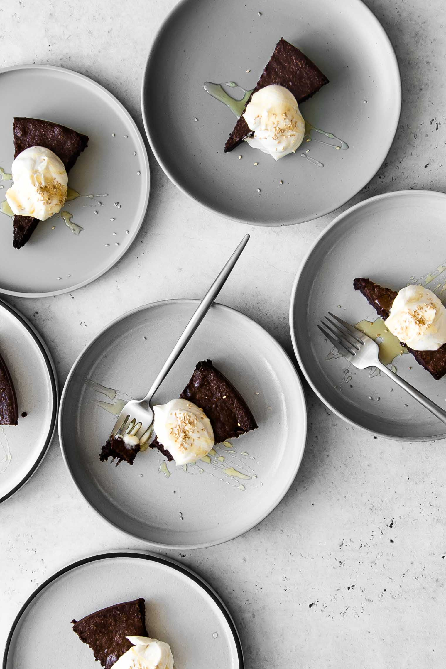 Six plates of flourless chocolate cake with whipped cream and sesame seeds