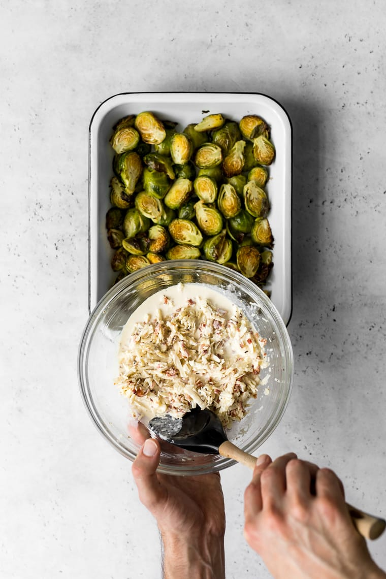bowl with gratin mixture being held above baking pan of roasted brussels sprouts