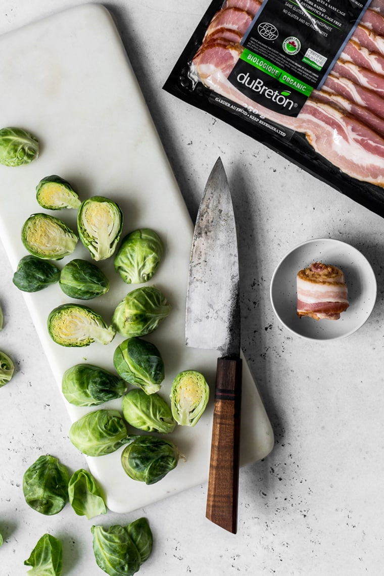 Marble board with sliced brussels sprouts  with knife and next to package of bacon and rolled piece of bacon in a small bowl