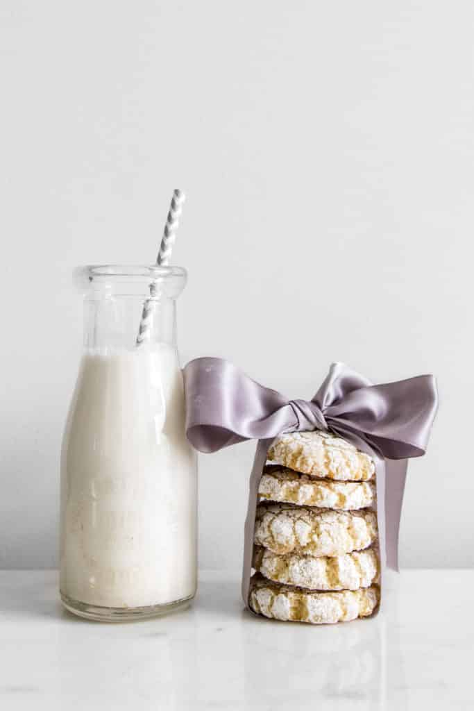 Bottle of milk next to a stack of amaretti cookies with purple ribbon around them