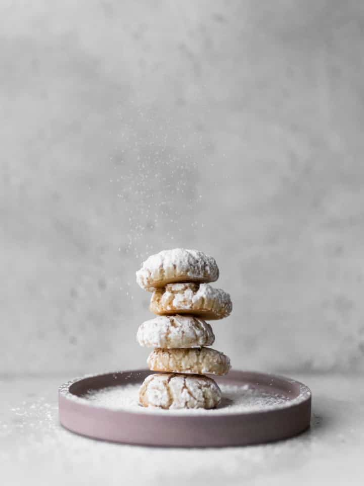 Five amaretti cookies stacked on a pink plate