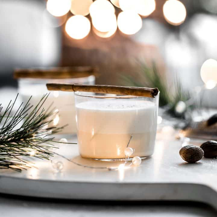 Eggnog with cinnamon stick on top with holiday decor in the background