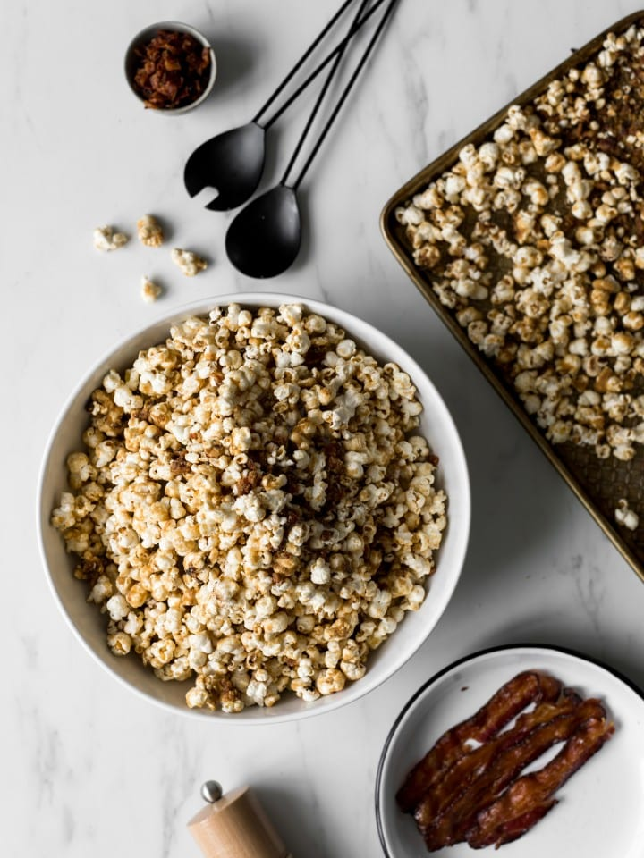 Bowl of maple and brown sugar popcorn with bacon, plate with bacon, black utensils