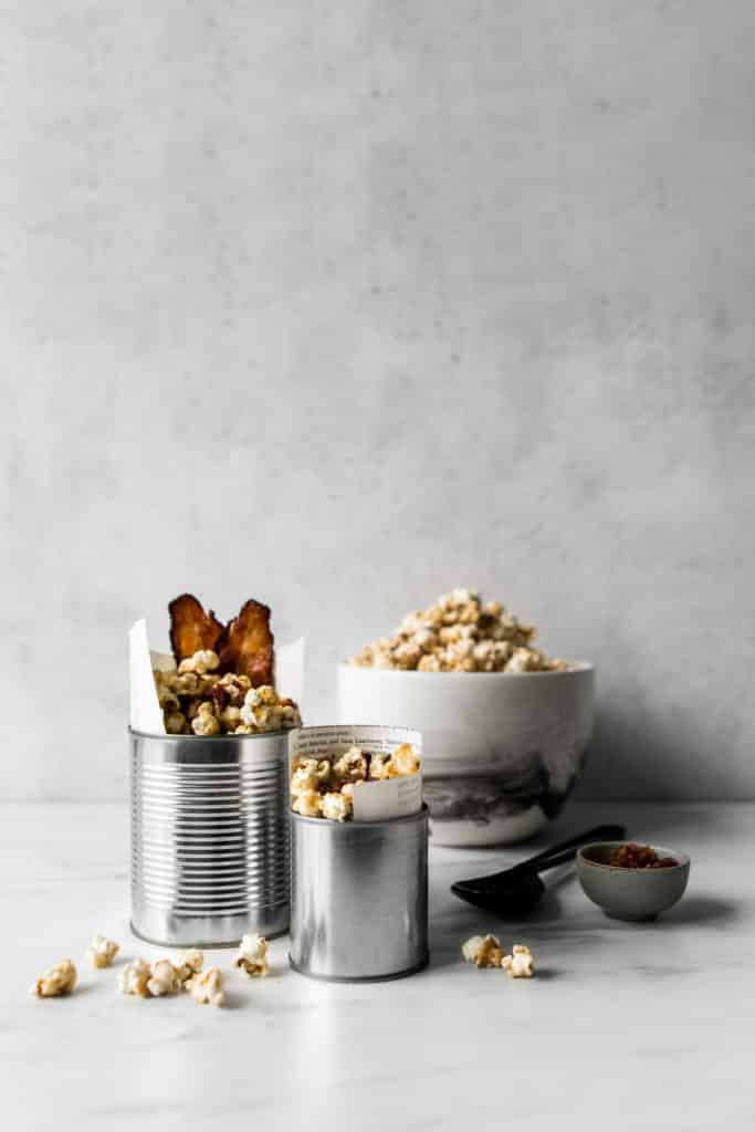 Two tins with Maple Bacon Popcorn in front of a bowl of maple caramel popcorn