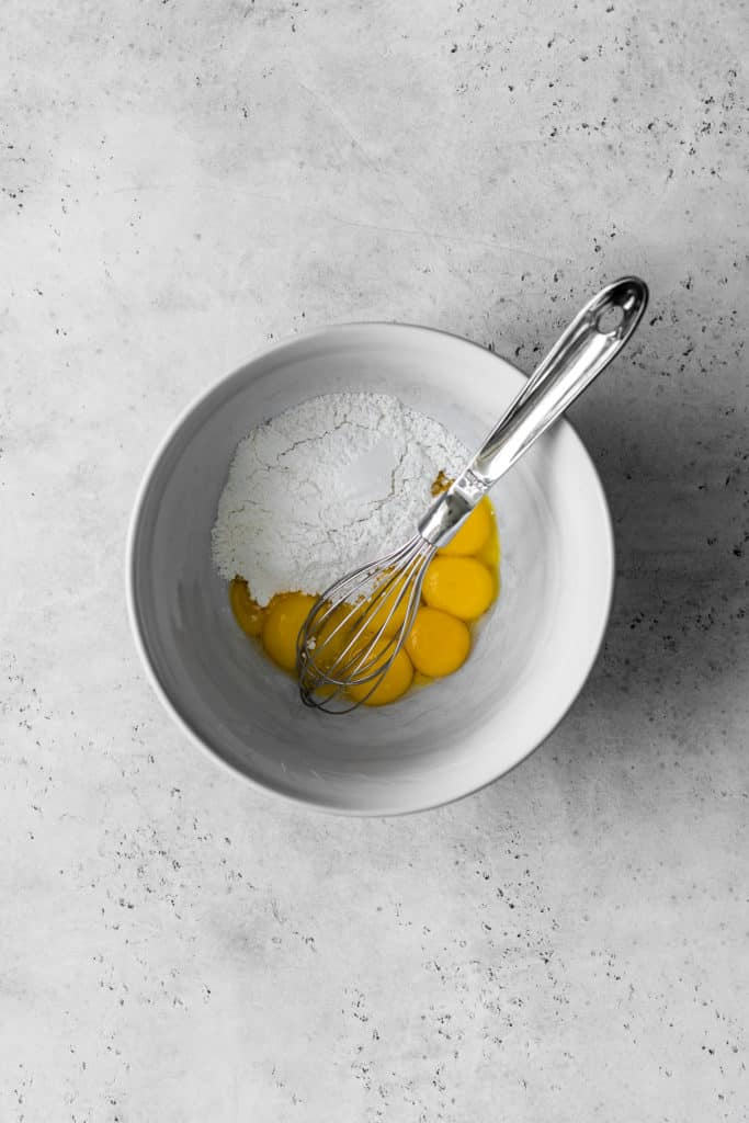 A bowl of egg yolks and icing sugar with a metal whisk