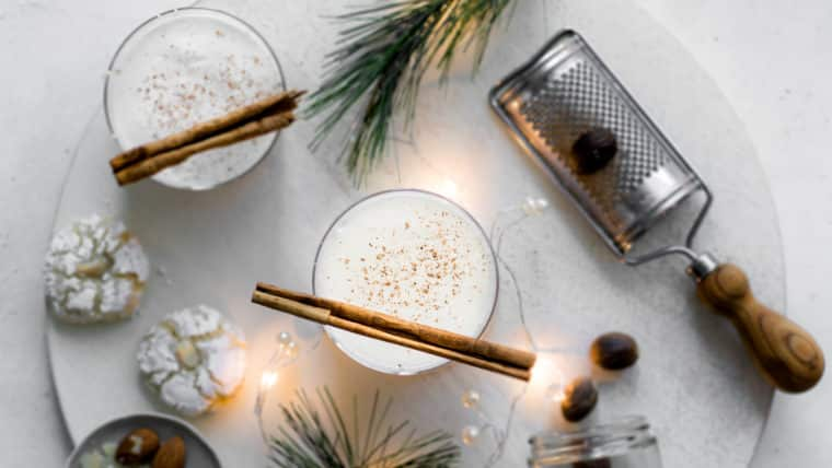 Two glasses of eggnog with cinnamon sticks, shot from above with nutmeg grater, cookies and pine leaves