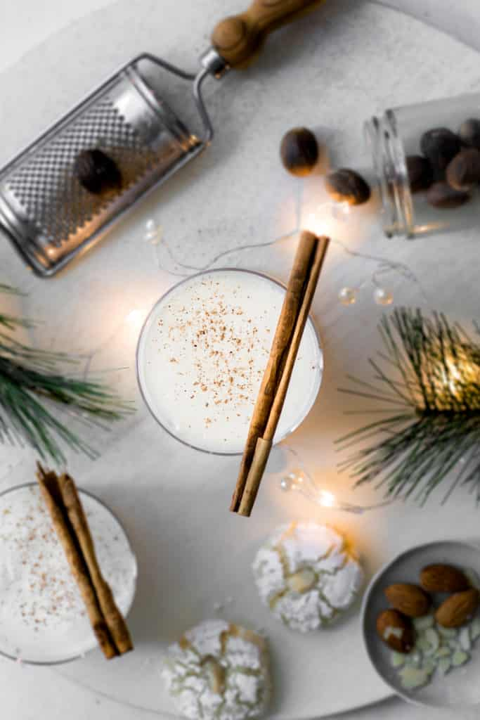 Two glasses of spiked eggnog with cinnamon sticks and cookies