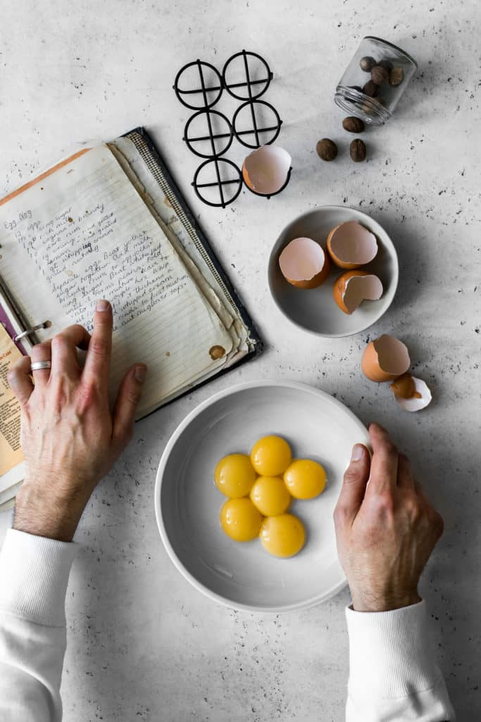 Hand pointing in an old handwritten recipe book, while other hand is holding a bowl of egg yolks
