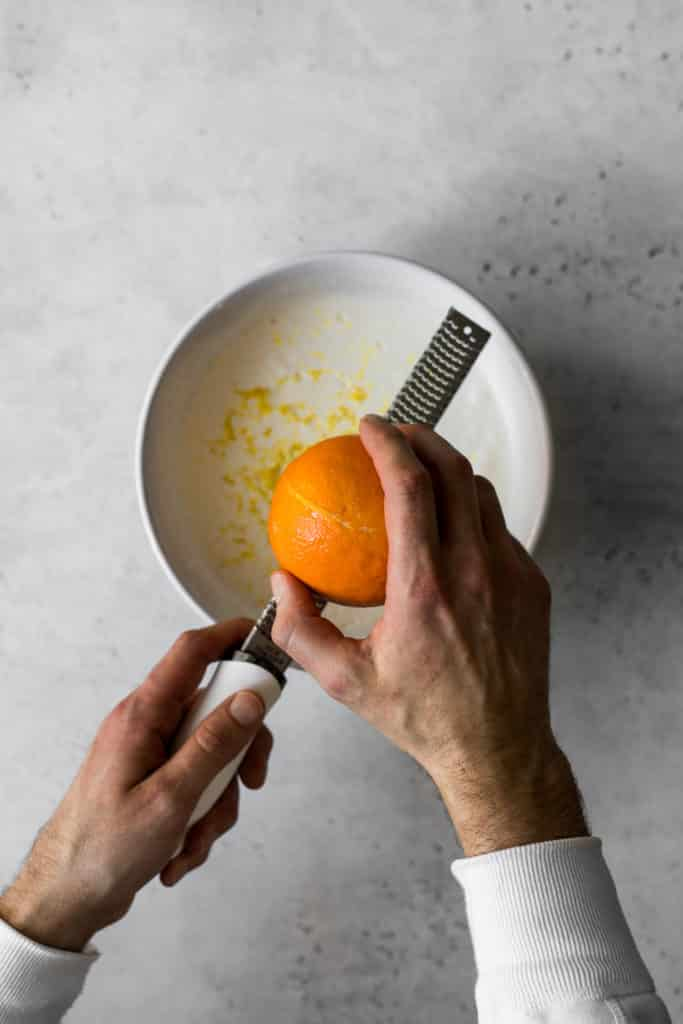 Hands zesting orange into cream with a microplane