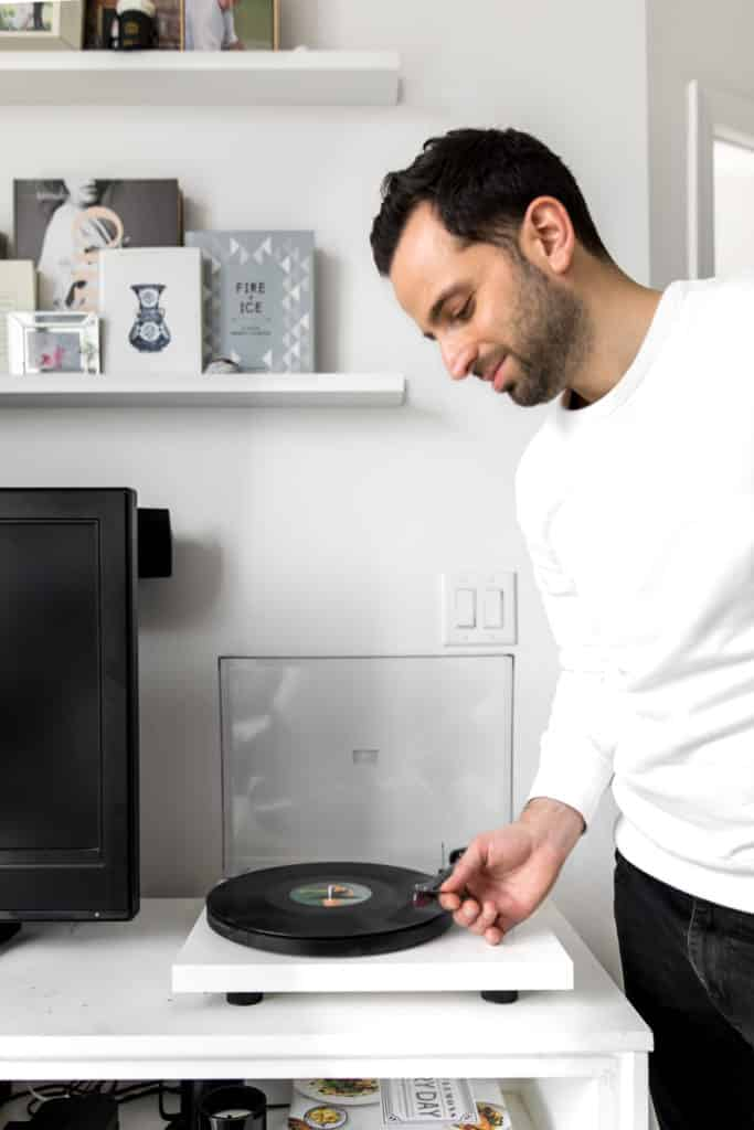 Person placing the needle on the record player to set the ambience for bringing the dining out experience in