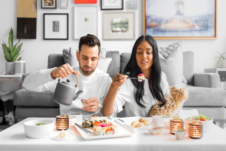 Interracial couple enjoying sushi sitting in front of their couch