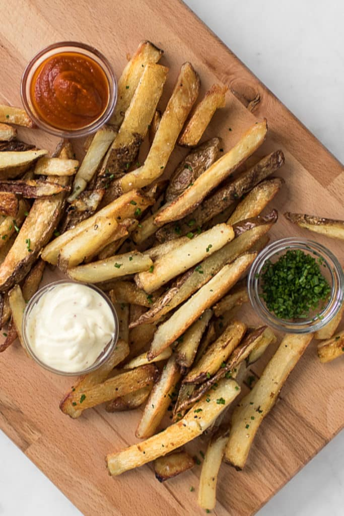 Crispy French Fries on a cutting board with ketchup, mayo, and chives