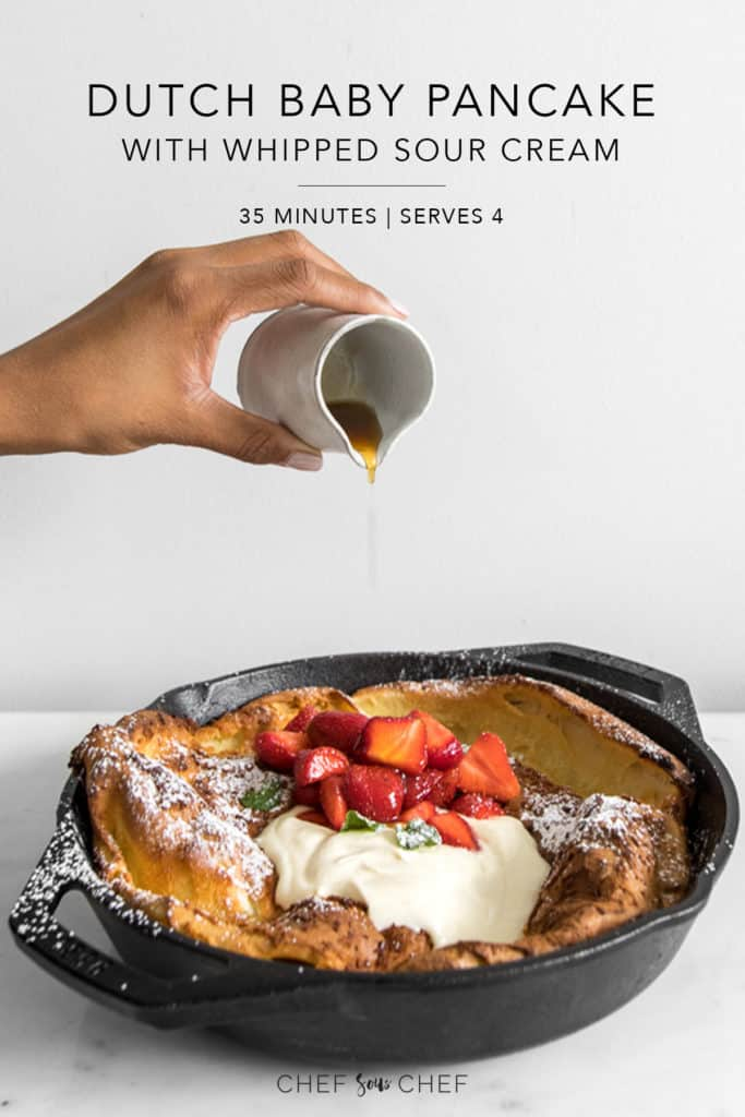 Dutch Baby Pancake in cast iron skillet with strawberries, whipped cream and a hand pouring maple syrup on top