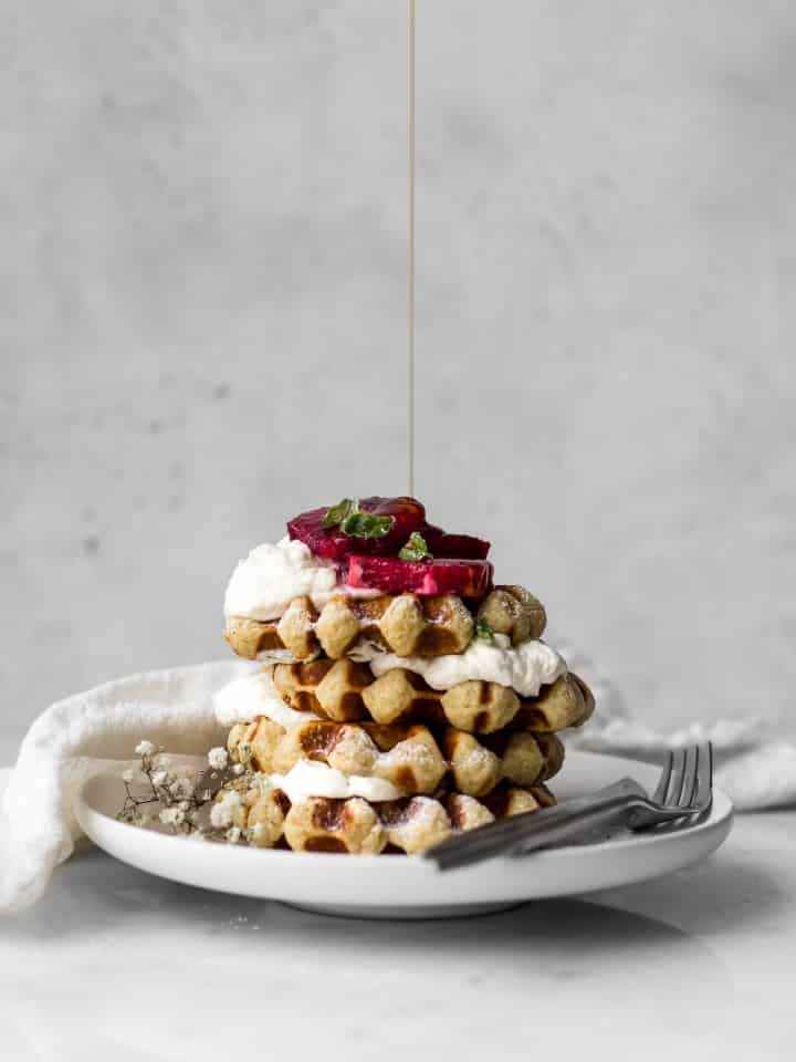 Belgian-Waffles with Whipped Cream and Blood Oranges getting Maple Syrup Drizzled on Top