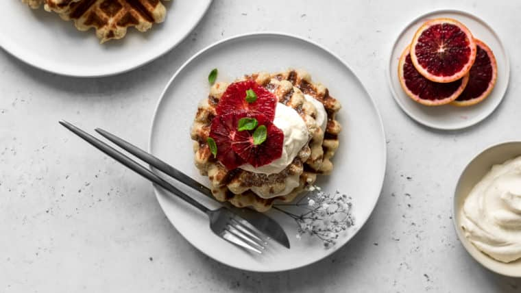 Plates with Belgian-Style Waffles, Blood Orange Slices and Whipped Cream