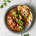 Butter Chicken with Coconut Milk in Silver Bowl with Cilantro and Naan