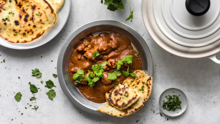 Butter Chicken in Silver Plate with Naan and Cilantro, next to Le Creuset Dutch Oven