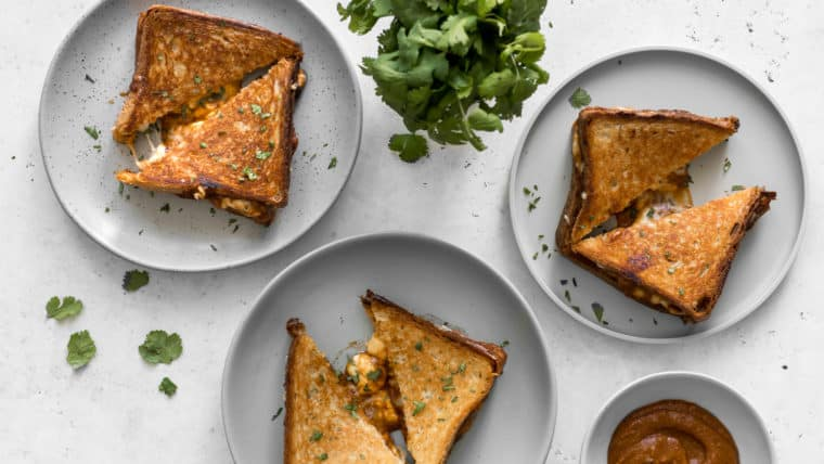 Three grilled cheeses on plates with butter chicken sauce and cilantro